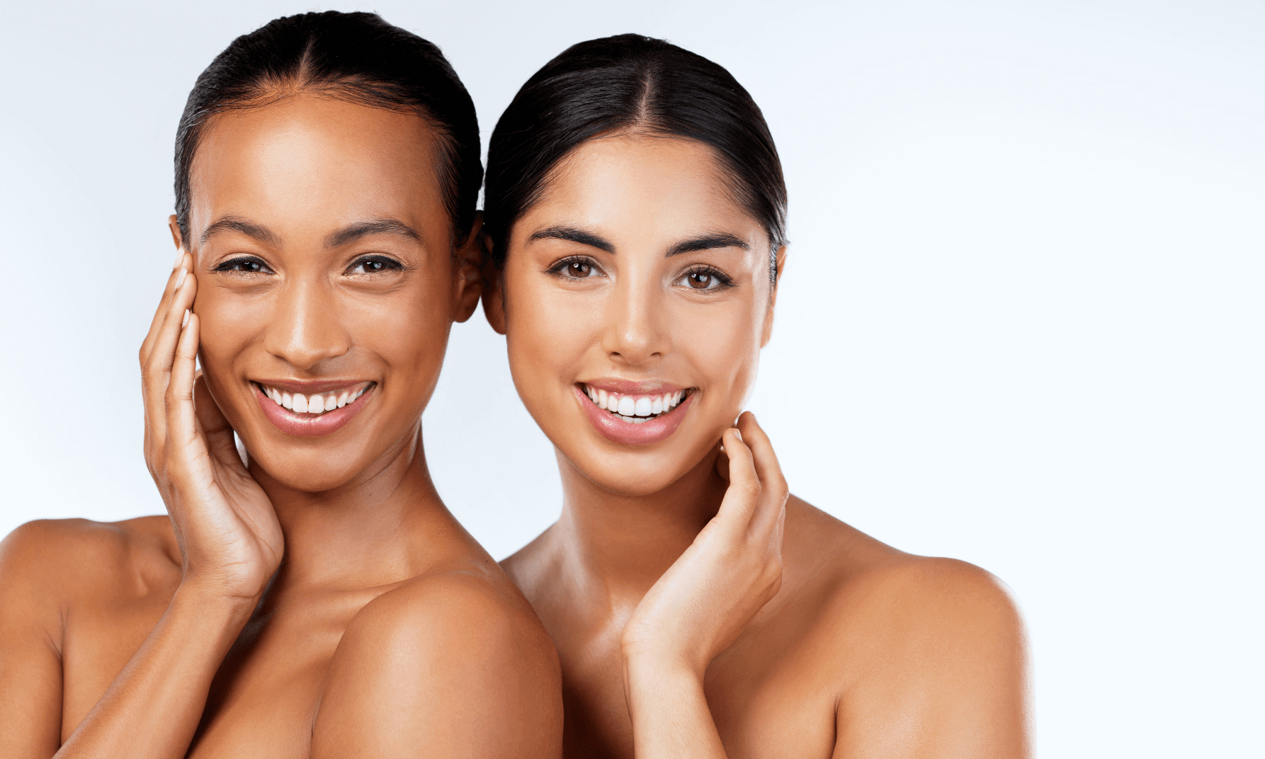 Two women smiling into the camera touching their faces after dermal fillers